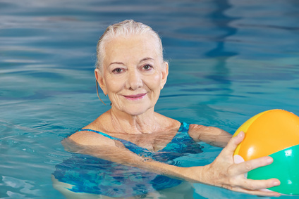 Happy senior woman with water ball in swimming pool doing aqua fitness