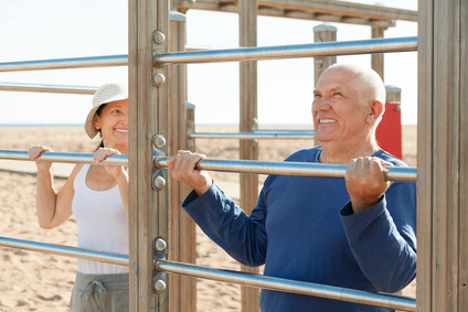 healthy senior couple together training on pull-up bar in summer